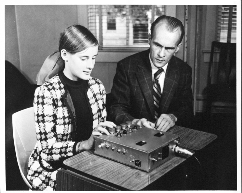 Female participant and male researcher sit at table in front of rectangular testing machine.