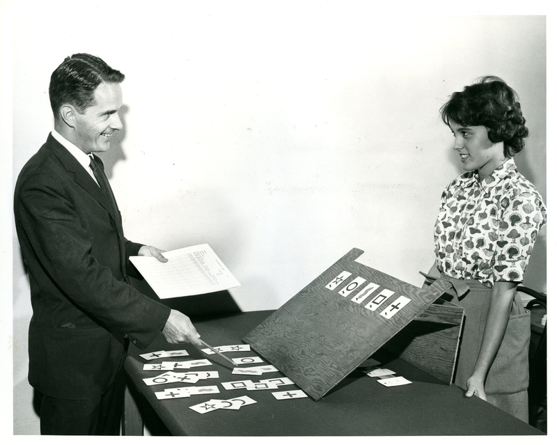 Female participant makes eye contact with smiling man holding paper and pointing to cards with symbols on them.