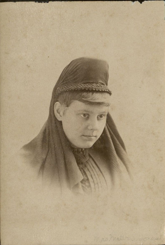 Sepia-toned photograph of a white woman wearing a dark headpiece covering most of her hair, perhaps in mourning