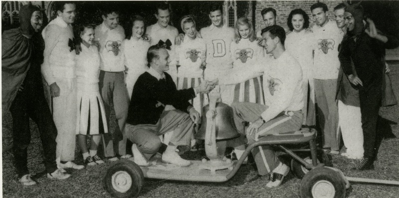 Head cheerleaders from Duke and UNC shake over the Victory Bell, surrounded by other cheerleaders and their respective mascots.  The Victory Bell is passed back and forth each year to the winner of the Duke-UNC football game.