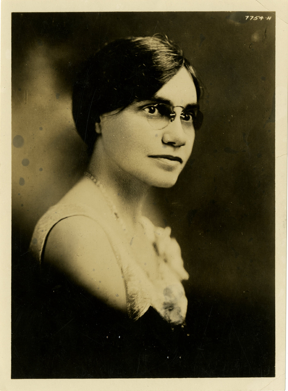 Sepia-toned portrait of a white woman with dark hair, wearing round glasses