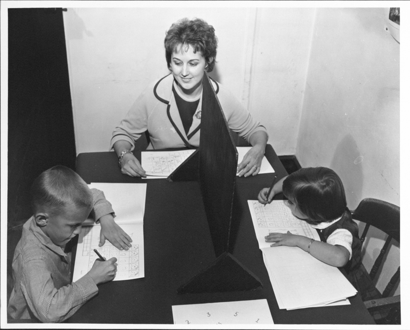 Two children sit at a table opposite each other, drawing, while a smiling woman observes.