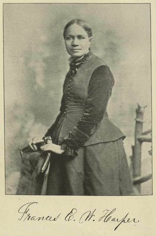 "Black and white printed photograph in book of a Black woman standing with her hands on the back of a chair, wearing a long black dress, handwritten cursive underneath reading ""Frances E. W. Harper"""