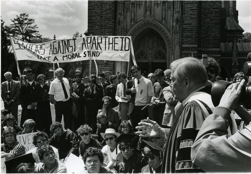President Terry Sanford talks to protesters at a graduation protest against the South African Apartheid.  Students built shantytowns on the quad and staged protests in hopes of pressuring the Board of Trustees to divest Duke assets from South African companies and companies sympathetic to apartheid.