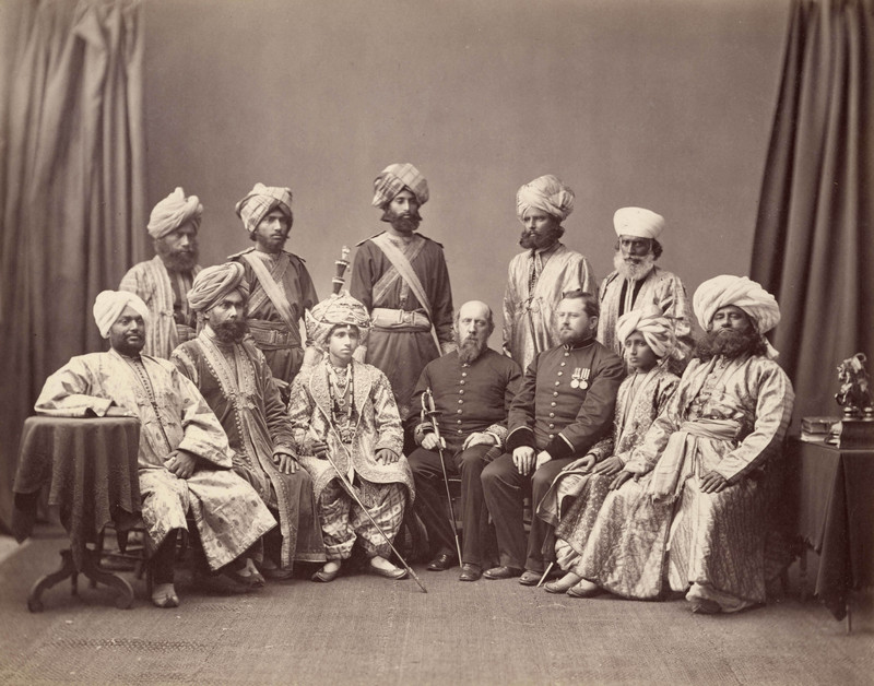 Studio group portrait of Indian men in full dress, and two English (?) military officers in uniform<br />