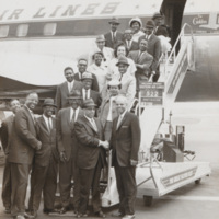 "Men and women standing on stairs leading to Eastern Air Lines airplane (Lockheed Constellation ""Super-G""). A sign says ""Welcome aboard Eastern Air Lines flight 522, destination New York La Guardia."" Possibly taken at Raleigh-Durham Airport?"