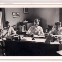 Three men sit at a large desk. One smokes a pipe, one writes in a notebook, and one observes an object.