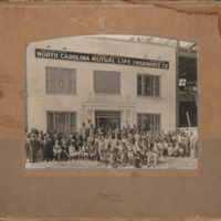 A large crowd of people pose in front of the two-story N.C. Mutual Building.  Sign reads: North Carolina Mutual Life Insurance Co. Health-life