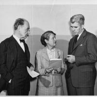 Man holding piece of paper and woman holding book stand in front of blank wall as another man speaks with them.