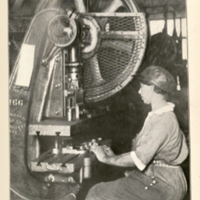 "Photograph in book of a Black women sitting and working at an industrial machine, wearing a cap. Caption underneath reads ""A new day for the colored woman worker - skilled work and skilled workman's wages"""
