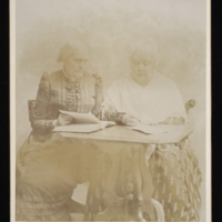 Faded sepia-toned portrait of two white women sitting together at a table, one is reading and one is writing, both are wearing long dresses