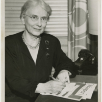 Black and white photograph of older white woman at adesk writing a note, wearing glasses, a black shirt, and a gold link necklace