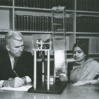 Older man sits at table taking notes while younger woman in a sari observes rectangular testing machine.
