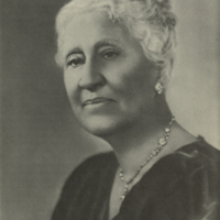 Portrait of a Black woman with white hair, wearing a sparkly necklace and earrings