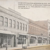 "Tinted postcard-style photograph of block of two- and three-story buildings on Parrish St., Durham, North Carolina. Caption reads: ""Home offices and business block of the North Carolina Mutual & Provident Association of Durham, N.C., the largest Negro insurance co. in the world."""