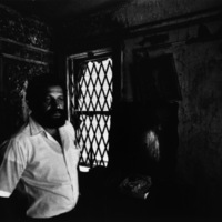 Community organizer José Acuña shows a building burned by arson, Manhattan Valley, Manhattan, NY 1981