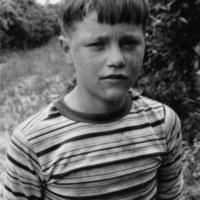 Migrant boy in orange grove, outside Tampa, FL, 1979<br /> <br /> John Moses Photographs<br /> gelatin silver print