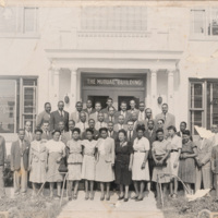 "A large group of men and women pose in front of a white building with ""The Mutual Building"" over the door."