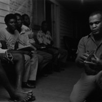 Donald Stokes teaching ESL to Haitian farmworkers Newton Grove, NC, Summer 1987<br /> <br /> Rob Amberg Photographs and Papers<br /> gelatin silver print