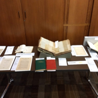 A long table with a variety of archival materials on display, including pamphlets and books